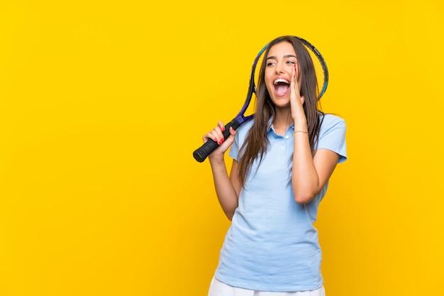 Junge tennisspielerfrau über der lokalisierten gelben wand, die mit dem breiten mund schreit, öffnen sich
