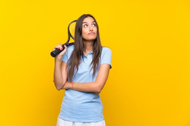 Junge tennisspielerfrau über der lokalisierten gelben wand, die zweifel macht, gestikulieren beim anheben der schultern