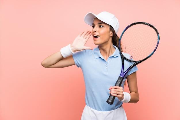Junge tennisspielerfrau über der lokalisierten rosa wand, die mit dem breiten mund schreit, öffnen sich
