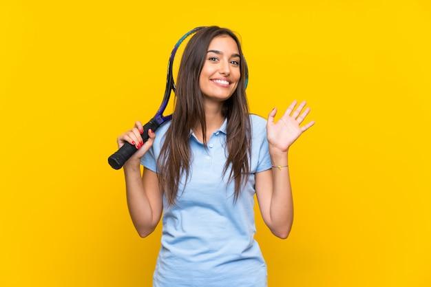 Junge tennisspielerfrau über lokalisierter gelber wand, die mit der hand mit glücklichem ausdruck begrüßt