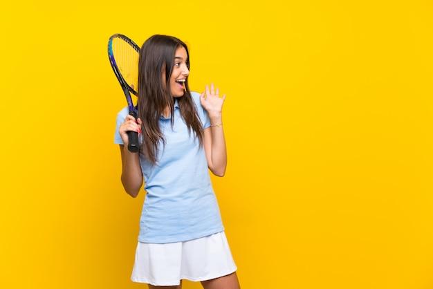 Junge tennisspielerfrau über lokalisierter gelber wand mit überraschungsgesichtsausdruck