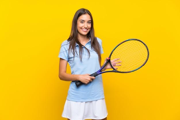 Junge tennisspielerfrau über lokalisierter gelber wand