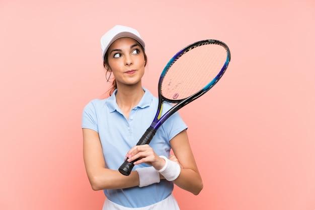 Junge tennisspielerfrau über lokalisierter rosa wand, die oben beim lächeln schaut