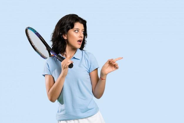 Junge tennisspielerfrau überrascht und seite zeigend