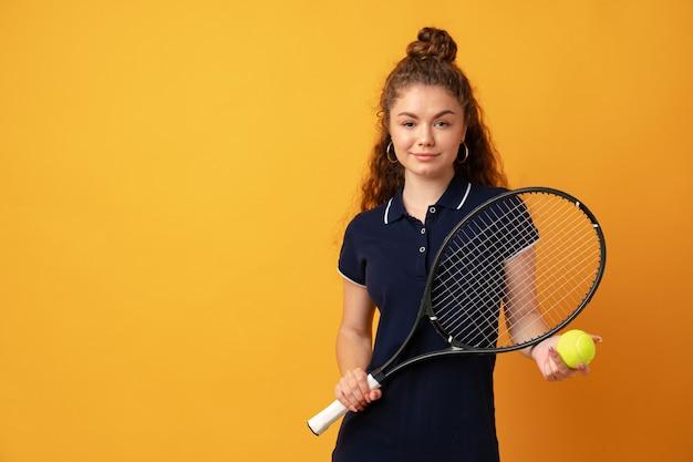 Junge tennisspielerin, die mit schläger vor gelbem hintergrund steht