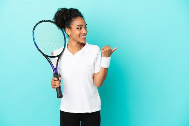 Junge tennisspielerin isoliert auf blauem hintergrund, die auf die seite zeigt, um ein produkt zu präsentieren