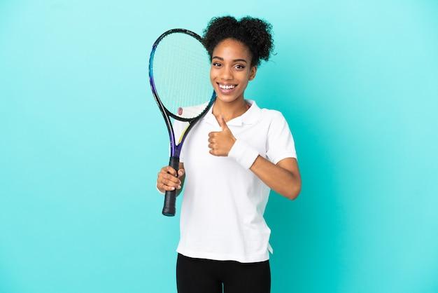 Junge tennisspielerin isoliert auf blauem hintergrund, die eine geste mit dem daumen nach oben gibt