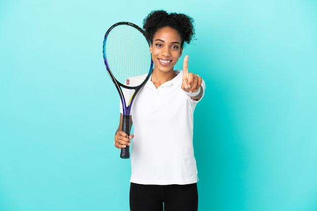 Junge tennisspielerin isoliert auf blauem hintergrund, die einen finger zeigt und hebt