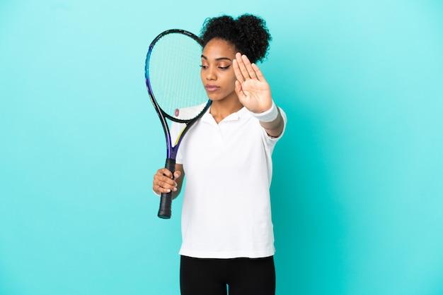 Junge tennisspielerin isoliert auf blauem hintergrund, die stop-geste macht und enttäuscht
