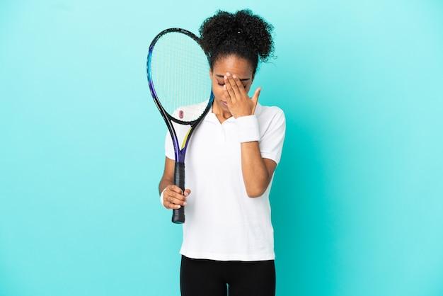Junge tennisspielerin isoliert auf blauem hintergrund mit müdem und krankem gesichtsausdruck