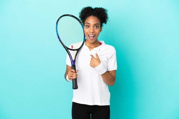 Junge tennisspielerin isoliert auf blauem hintergrund mit überraschtem gesichtsausdruck