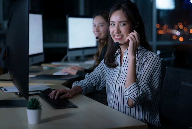 Junge thailändische asiatische kundendienstmitarbeiter, die in der nachtschicht im call center arbeiten, um kunden nachts am arbeitsplatz zu unterstützen
