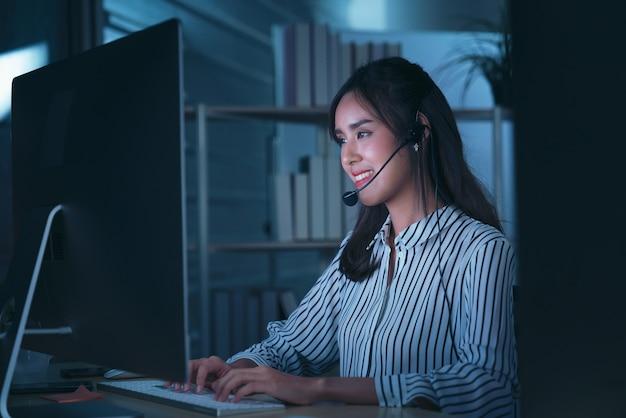 Junge thailändische asiatische kundendienstmitarbeiter, die nachtschicht im callcenter arbeiten
