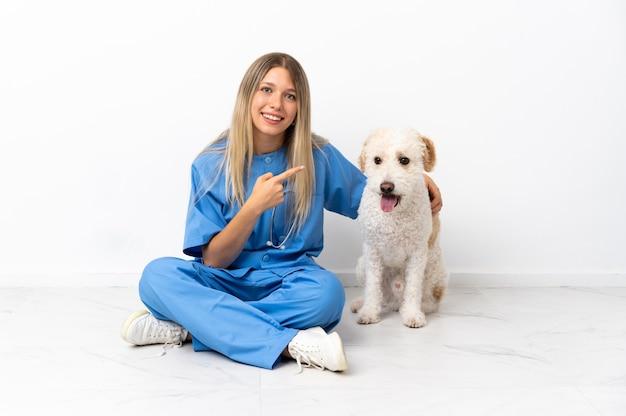 Junge tierarztfrau mit hund, der auf dem boden sitzt, der zur seite zeigt, um ein produkt zu präsentieren
