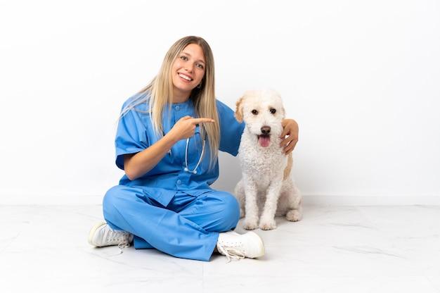 Junge tierarztfrau mit hund, der auf dem boden sitzt und finger zur seite zeigt