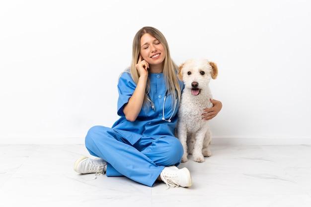Junge tierarztfrau mit hund, der auf dem boden sitzt