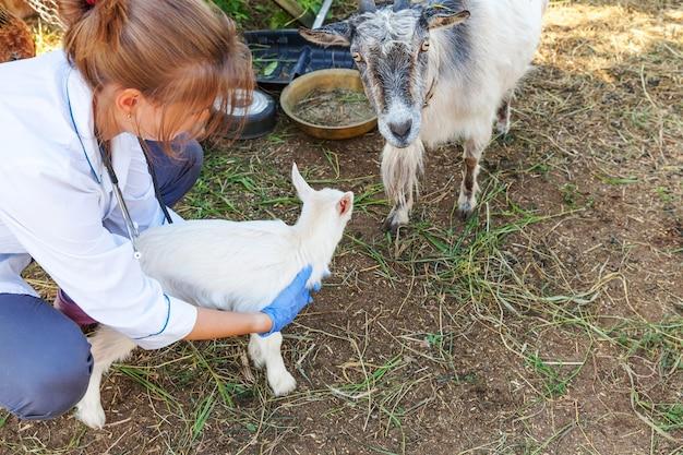 Junge tierarztfrau mit stethoskop, die ziegenkind auf ranchhintergrund hält und untersucht. junge ziegen in tierarzthänden zur untersuchung in einer natürlichen öko-farm. moderne tierhaltung, ökologische landwirtschaft.