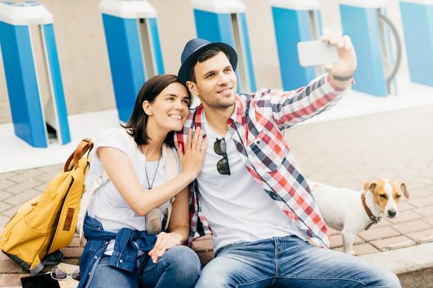 Junge touristen, die auf pflasterung sitzen, selfie mit intelligentem telefon machen, an der kamera mit glücklichem ausdruck aufwerfen und stehen still, nachdem sie museum oder kunstgalerie besucht haben. männliches und weibliches stillstehen, fotografierend