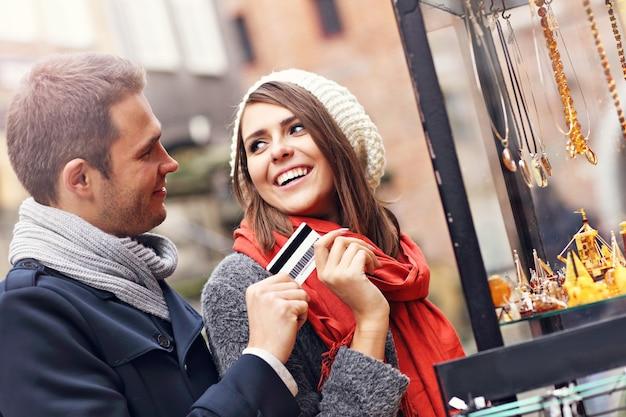 Junge touristen einkaufen für souvenirs mit kreditkarte in danzig