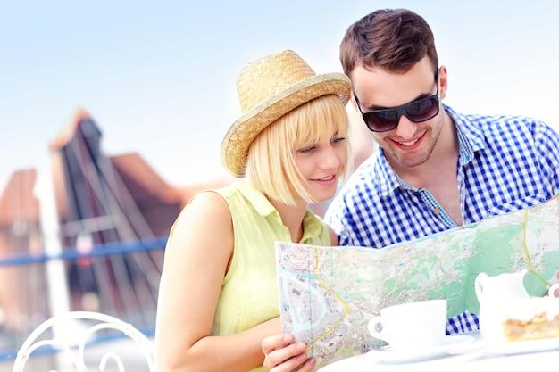 Junge touristen sitzen mit einer karte in einem café