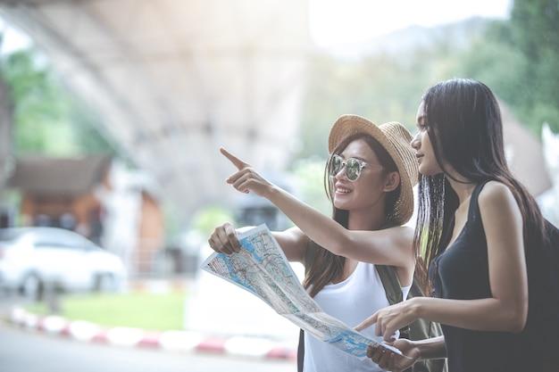 Junge touristen zeigen auf karte.