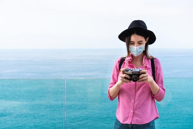 Junge touristenfrau, die alte weinlesekamera beim tragen der gesichtsmaske verwendet