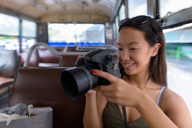 Junge touristenfrau, die am bus sitzt, während dslr-kamera verwendet