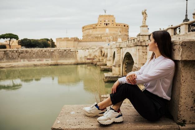 Junge touristenfrau, die auf dem alten damm tiber in roma sitzt