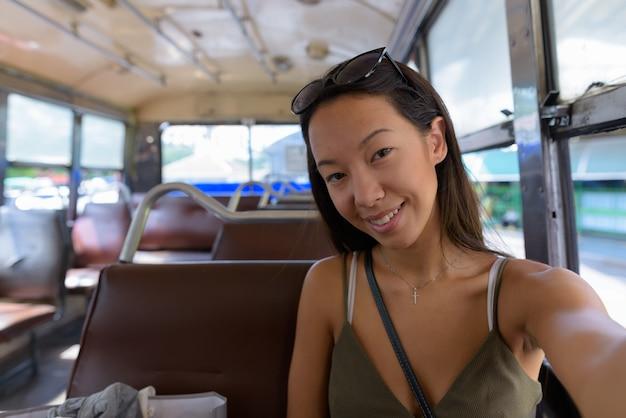 Junge touristenfrau, die die stadt bangkok mit bus erkundet