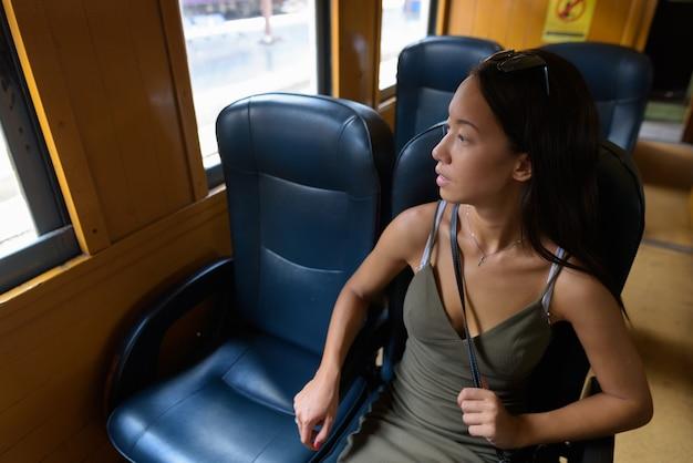 Junge touristenfrau, die die stadt bangkok mit zug erkundet