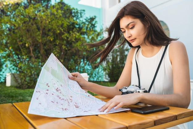 Junge touristenfrau, die karte am kaffeehaus betrachtet.