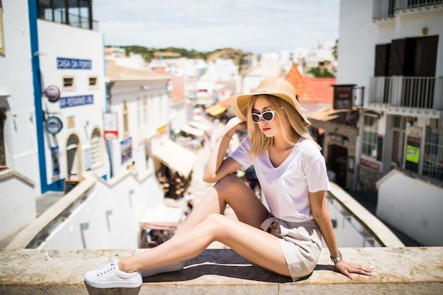 Junge touristenfrau im hut, der auf handlauf oben auf der stadt sitzt und panoramablick genießt