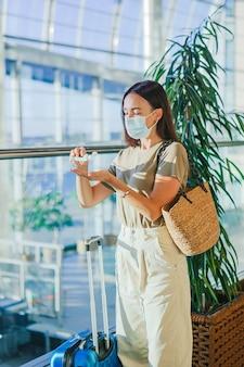 Junge touristenfrau in der medizinischen maske im internationalen flughafen