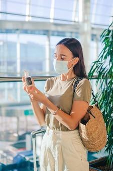 Junge touristenfrau in der medizinischen maske mit gepäck im internationalen flughafen