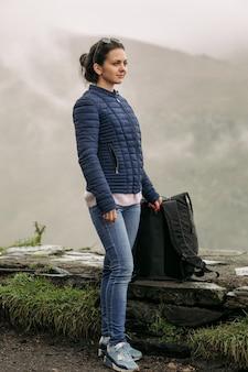 Junge touristenfrau mit einem rucksack gegen den hintergrund des kaukasusgebirges, georgia an einem nebligen tag