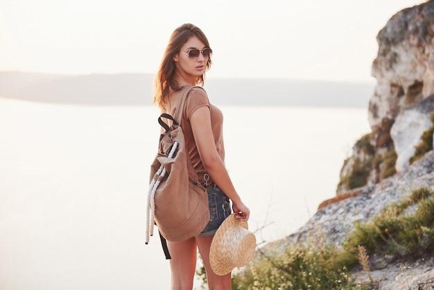 Junge touristenfrau oben auf der montage und blick auf eine schöne buchtlandschaft. wanderfrau mit rucksack, der sich auf der spitze der klippe entspannt