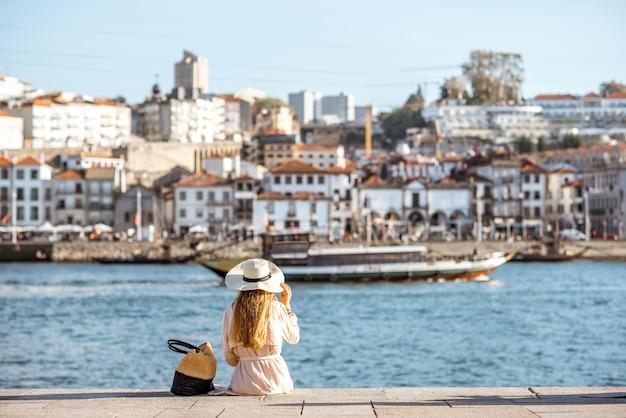 Junge touristin, die sich an der promenade von ribeira zurücklehnt und am sonnigen tag in portugal den blick auf das stadtbild auf die stadt porto genießt?