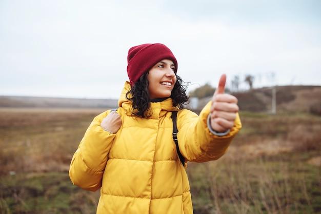 Junge touristin fängt ein auto auf der winterstraße weit weg von der stadt. konzentriere dich auf das gesicht. frau trägt gelbe jacke, rucksack und einen roten hut.
