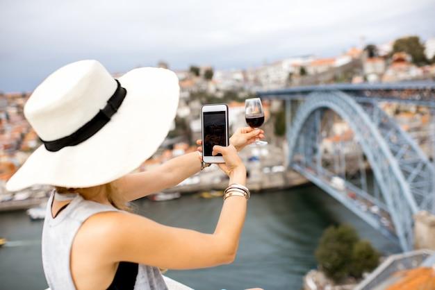 Junge touristin fotografiert ein glas porto-wein auf der terrasse mit tollem blick auf die stadt porto in portugal