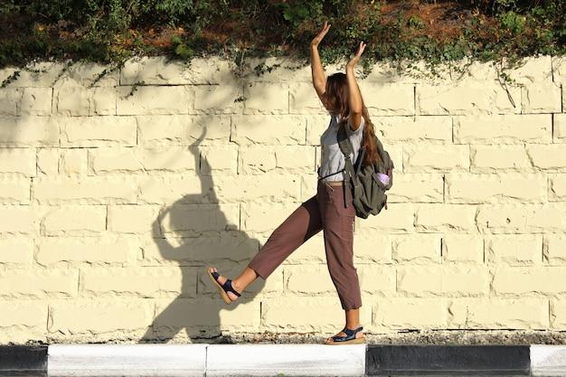 Junge touristin geht fröhlich am bordstein entlang der straße