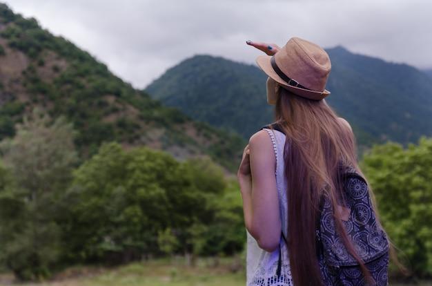 Junge touristin im strohhut untersucht die ferne in der natur. rückansicht. allein reisen konzept.