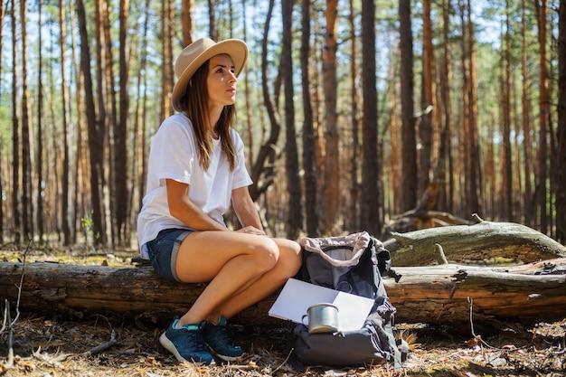Junge touristin in hut und t-shirt sitzt auf einem baumstamm während eines haltes im wald.