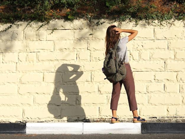 Junge touristin steht mit dem rücken auf dem bordstein an der straße und glättet ihr haar