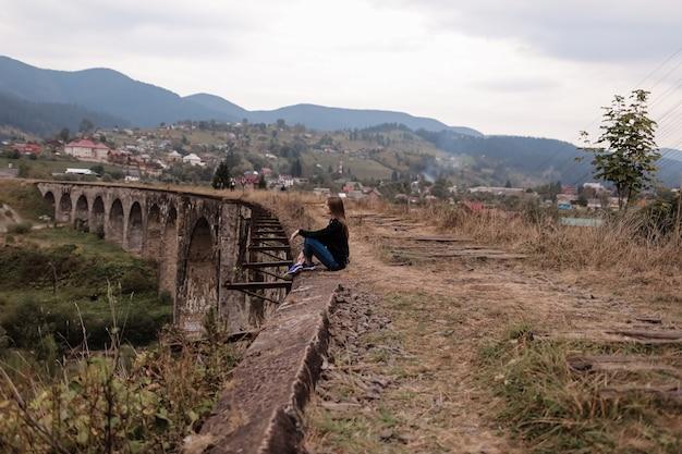Junge touristische frau, die auf viadukt mit alten eisenbahnlinien sitzt