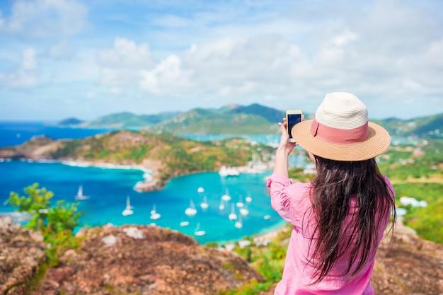 Junge touristische frau, die foto vom englischen hafen von shirley heights, antigua, paradiesbucht in tropeninsel im karibischen meer macht