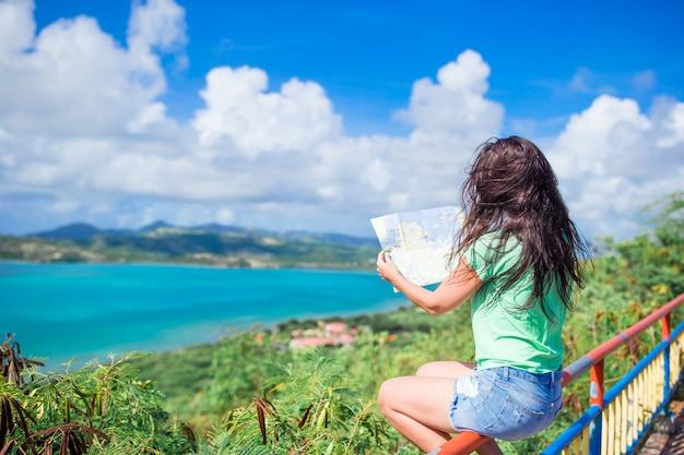 Junge touristische frau mit ansicht der bucht in tropeninsel im karibischen meer