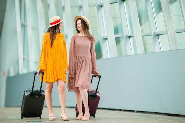 Junge touristische frauen mit gepäck im internationalen flughafen gehend mit ihrem gepäck.