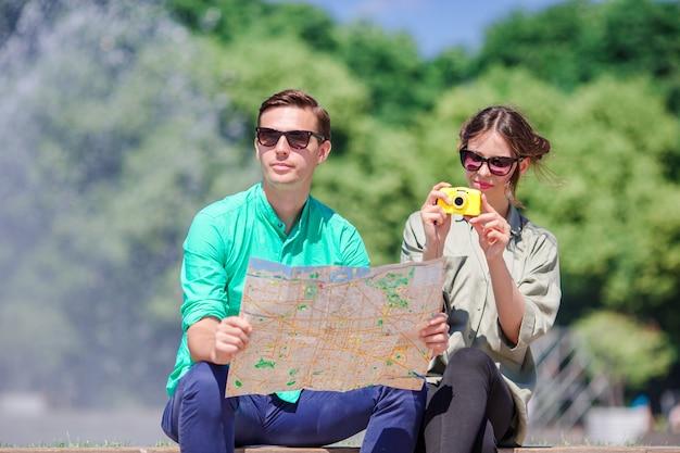 Junge touristische freunde, die an den feiertagen in europa lächeln glücklich reisen. kaukasische paare mit stadtplan auf der suche nach anziehungskräften