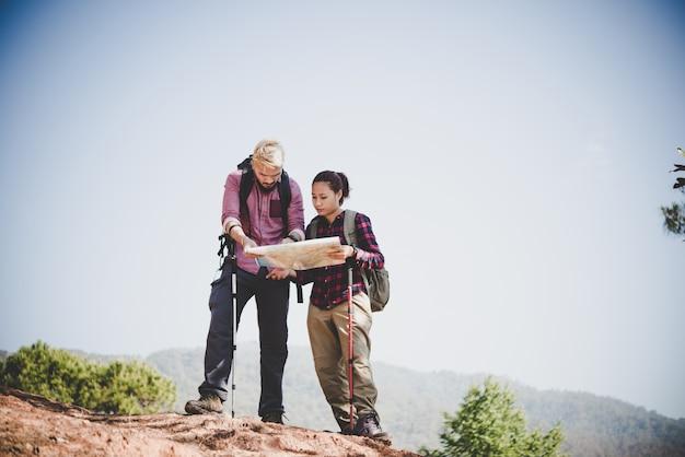 Junge touristische paar reisen auf urlaub in berg blick auf karte auf der suche nach attraktionen. reisekonzept