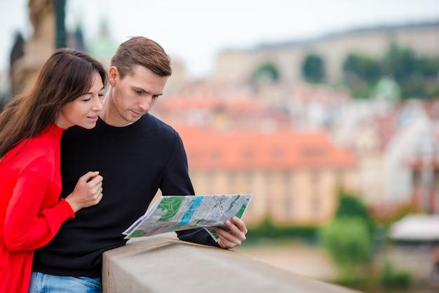 Junge touristische paare, die an den feiertagen in europa lächeln glücklich reisen. kaukasische familie mit stadtplan auf der suche nach anziehungskräften